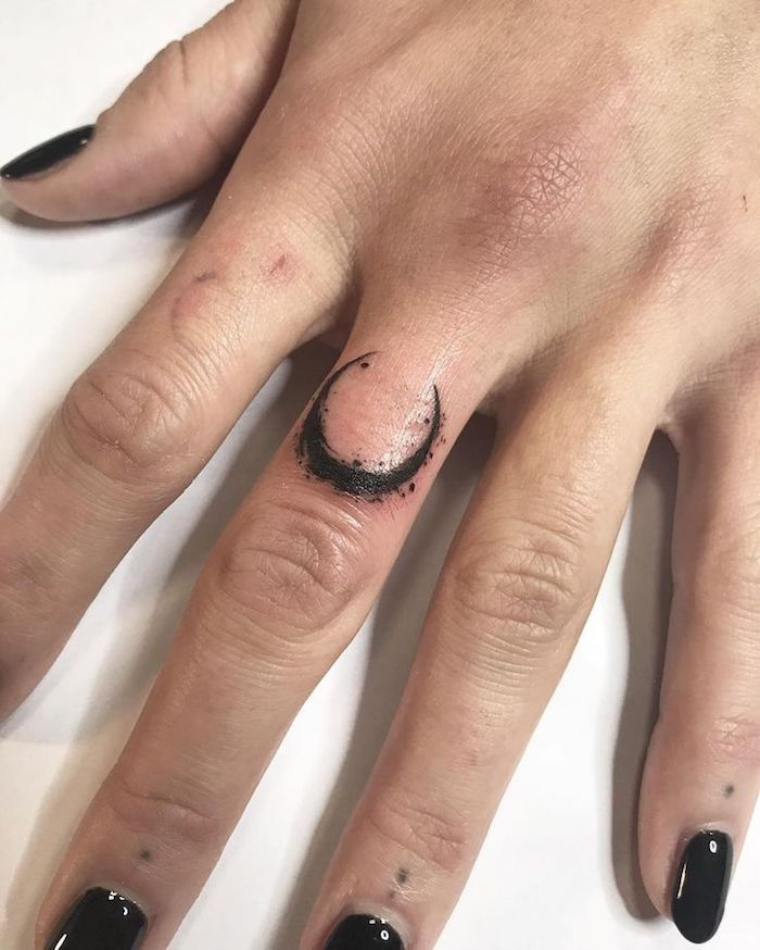 crescent moon tattoo, on the middle finger, finger tattoos, hand resting on a white countertop
