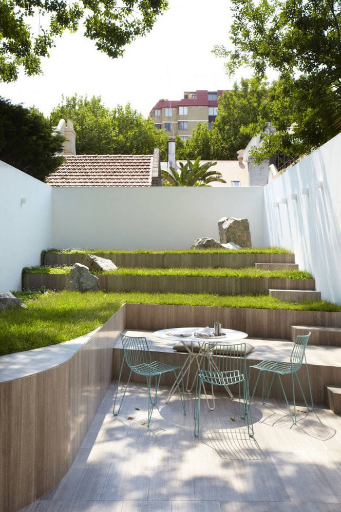 multi-leveled planted green grass, with large rocks, small garden ideas, metal garden furniture, on a wooden floor