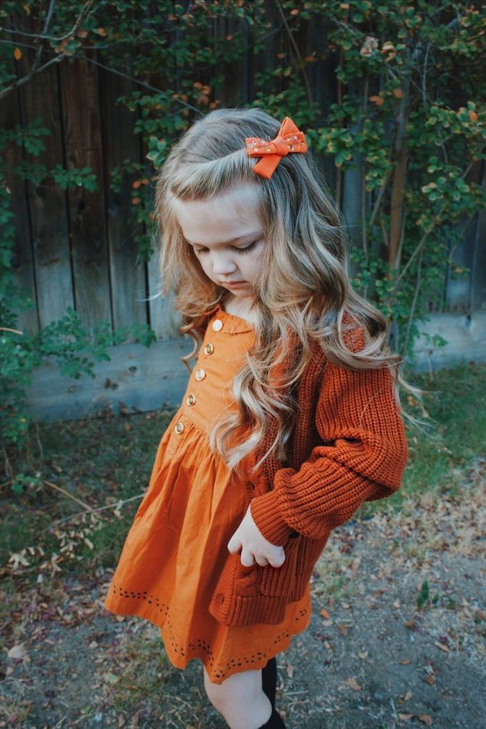 orange bow, long blonde wavy hair, hairstyles for girls with long hair, orange cardigan and dress