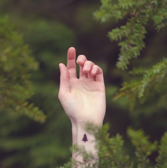 pine tree wrist tattoo, small butterfly tattoos, hand amongst pine trees in a forest