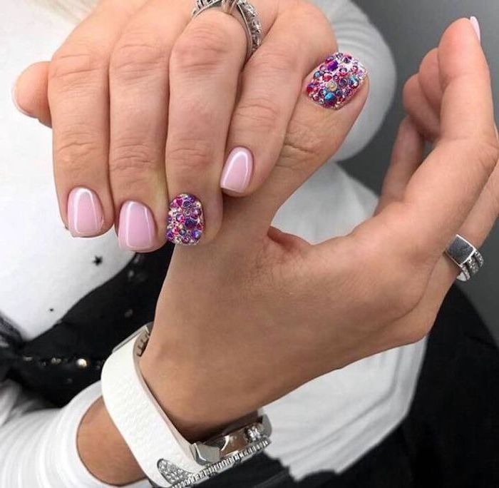pink nail polish, colourful rhinestones on two nails, white watch on the wrist, nude matte nails