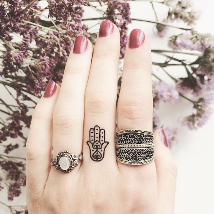 hand tattoo, middle finger tattoo, silver rings, red nail polish, lion finger tattoo, flowers in the background