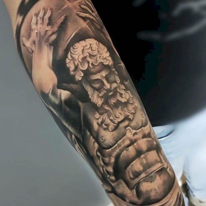 religious theme, forearm tattoo, man holding a weight, cool tattoos for guys, man wearing black shirt and jeans