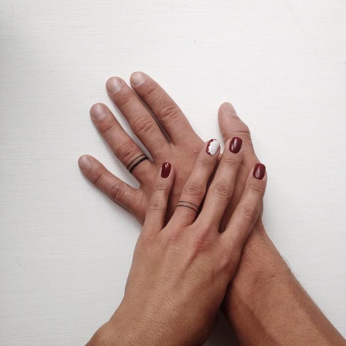 redd nail polish, lion finger tattoo, his and hers rings tattoo, female hand on top of a male hand