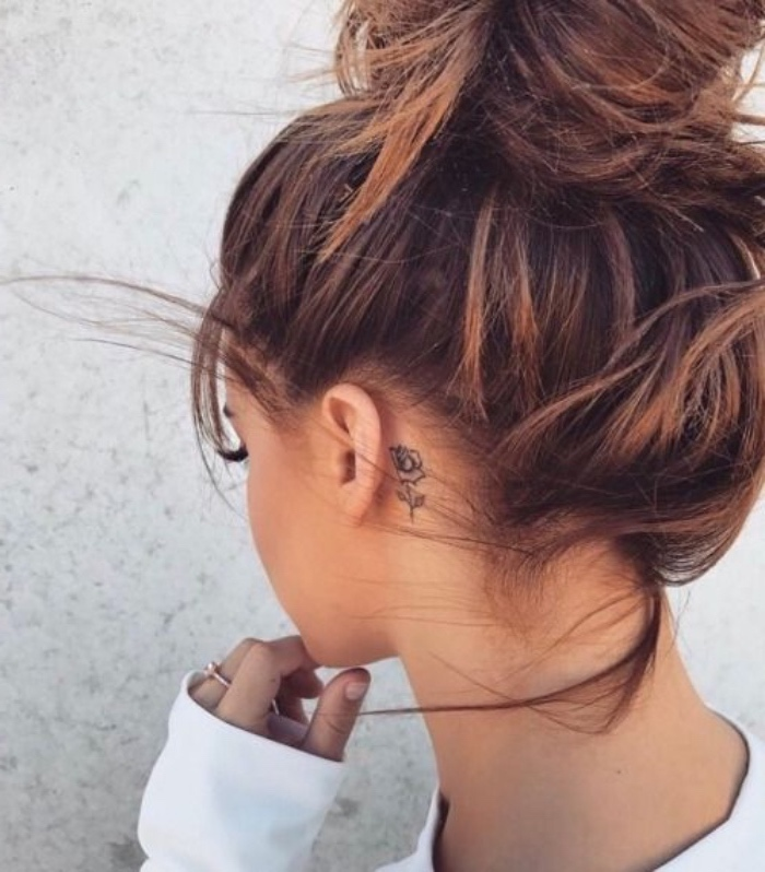 brown hair in a messy bun, small tattoo, small rose behind the ear tattoo, white blouse