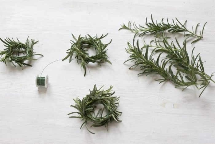 diy easter decorations, rosemary branches, with a green string, on a wooden countertop