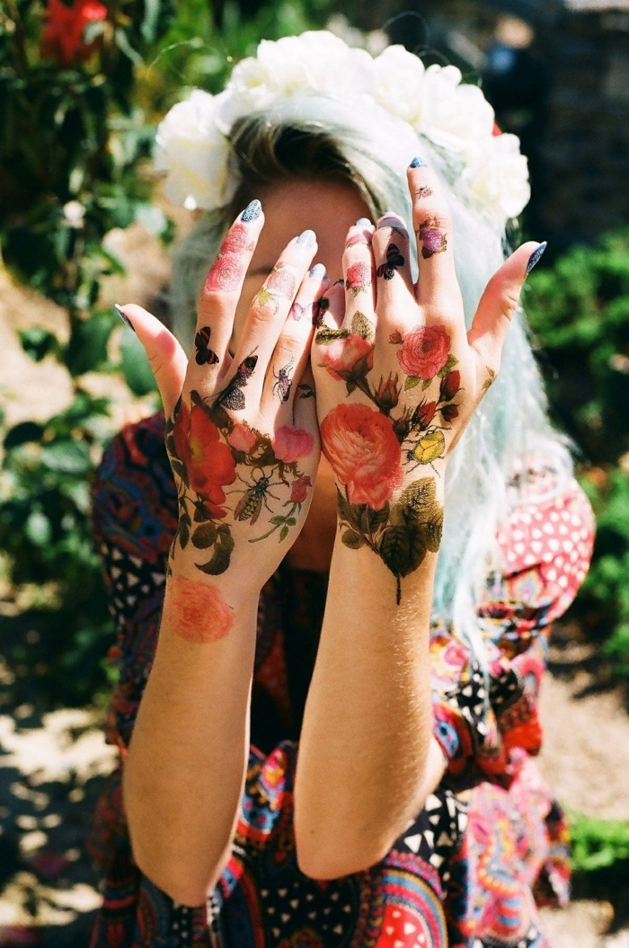 girl wearing a floral dress, rose finger tattoo, roses butterflies and bees, large tattoos on both hands