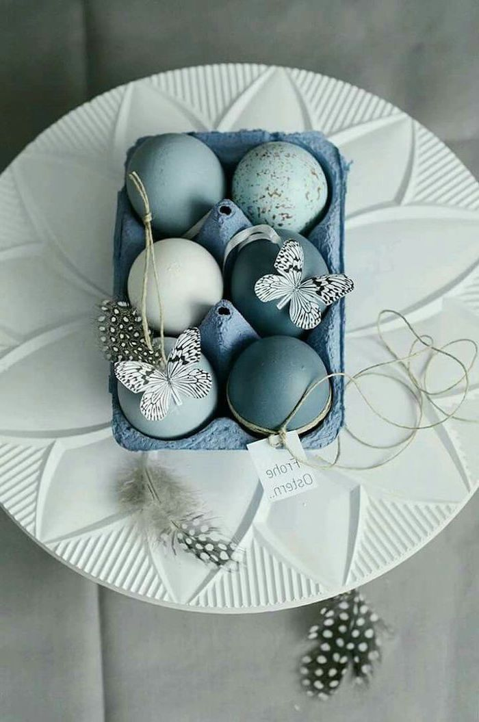blue egg carton, on a white plate, tie dye easter eggs, full of shades of blue eggs, butterflies and feathers
