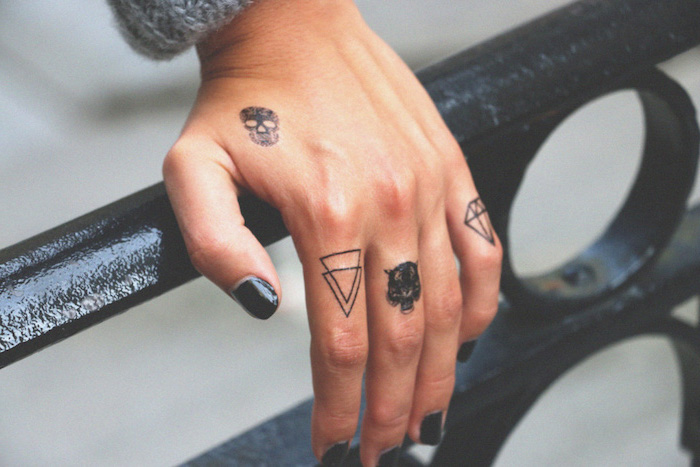hand resting on a metal railing, lots of different tattoos on the fingers, black nail polish, finger tattoos
