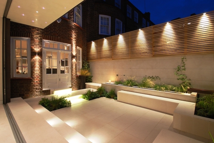 small backyard ideas, lots of lights, cement tiled floor benches, planted bushes flowers and trees