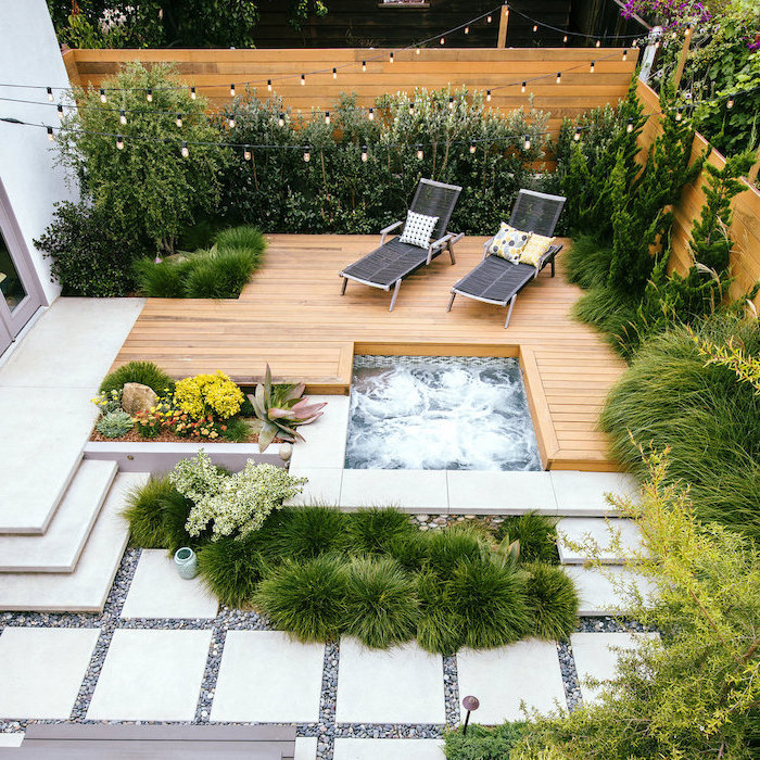 cement tiles, leading to a small hot tub, two lounge chairs, small backyard ideas, planted trees and bushes