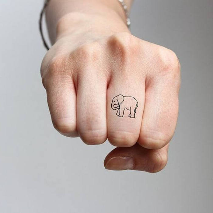 small elephant, middle finger tattoo, couple finger tattoos, hand in a fist, in front of a grey background