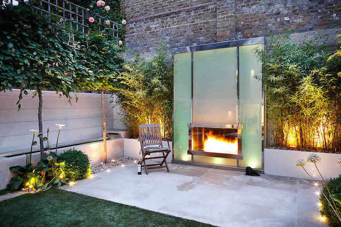 large fireplace, a small chair next to it, on a cement floor, small backyard landscaping, planted trees bushes and flowers