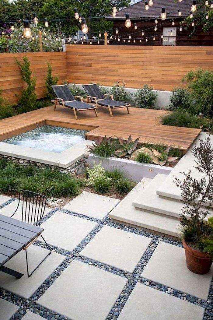small hot tub, surrounded by wooden floor, with two black lounge chairs, small backyard landscaping