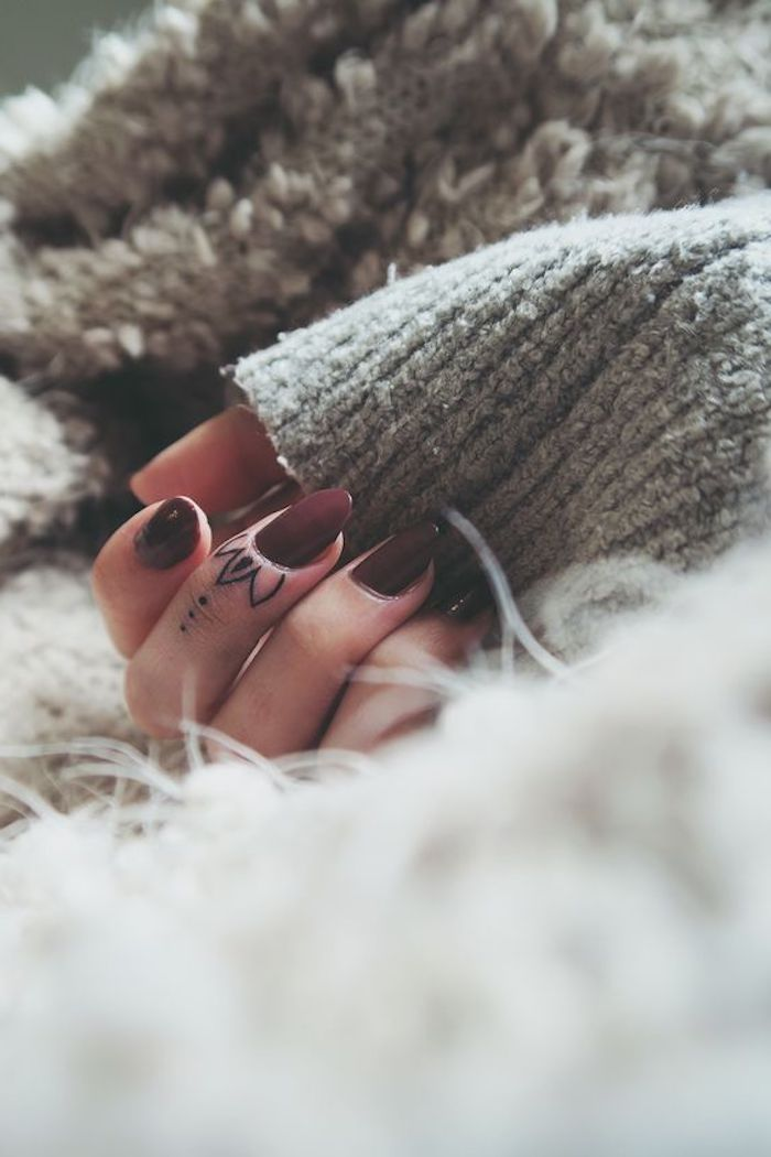 lotus flower middle finger tattoo, finger tattoo, burgundy nail polish, hand resting on a grey blanket