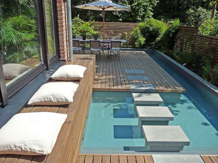 small swimming pool, cement tiles over it, small backyard landscaping, wooden bench, with white throw pillows