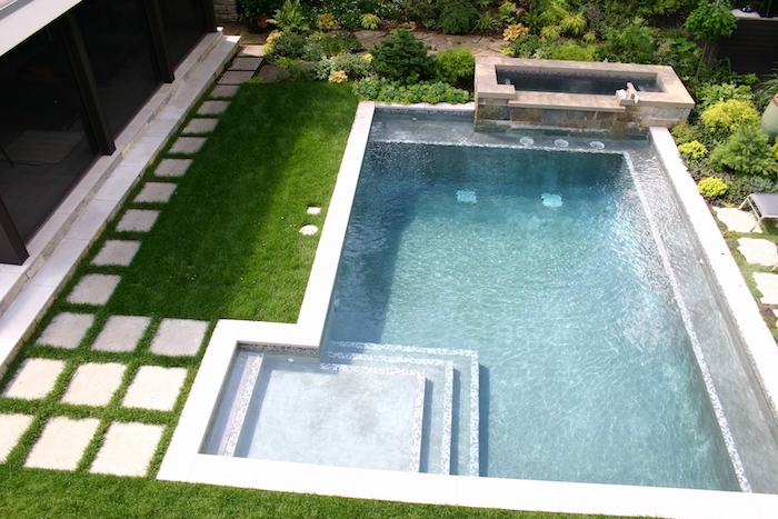 small swimming pool, with a small hot tub, small yard landscaping, ceramic tiles over a grass patch