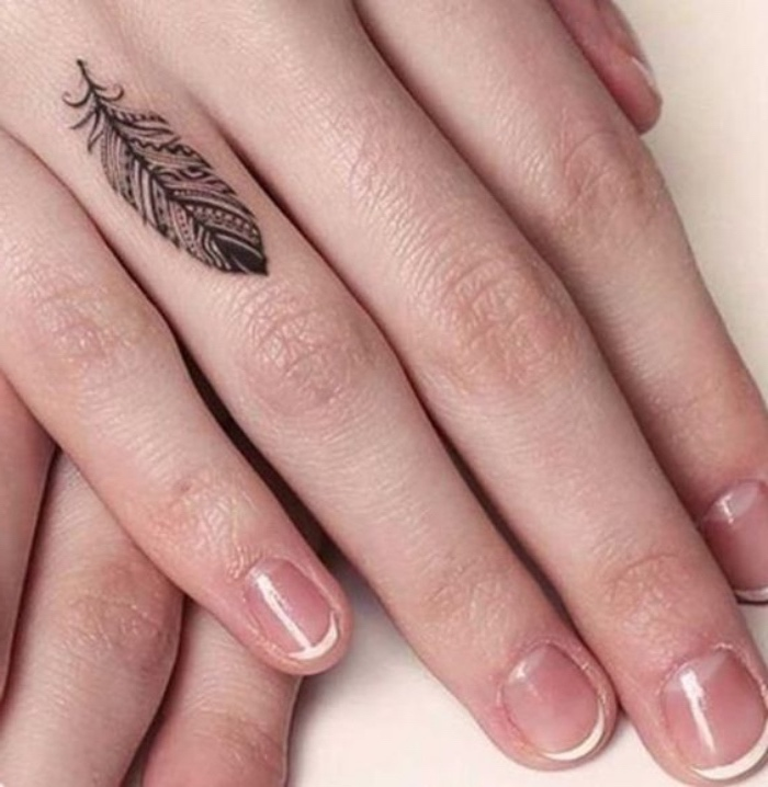 small black feather finger tattoo, small forearm tattoo, woman with a french manicure