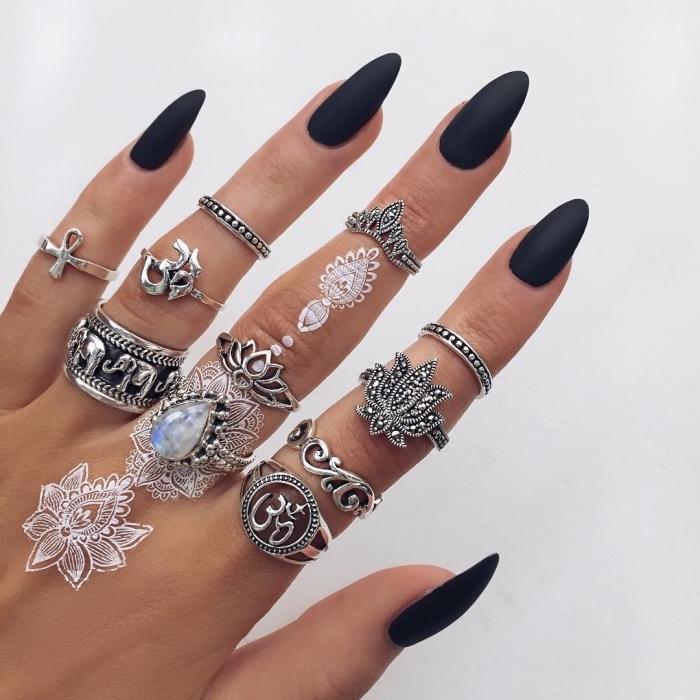 black matte nail polish, white henna tattoos, lots of silver stackable rings, crown finger tattoo