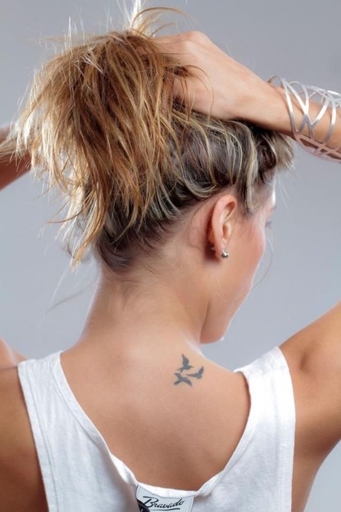 three birds flying back tattoo, woman tying her hair in a ponytail, small tattoo ideas for women, wearing a white top