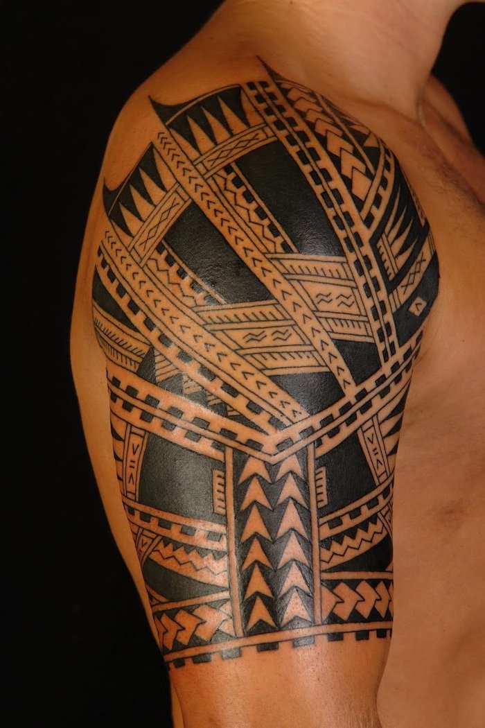 tribal shoulder tattoo, meaningful tattoos, man standing, in front of a black background