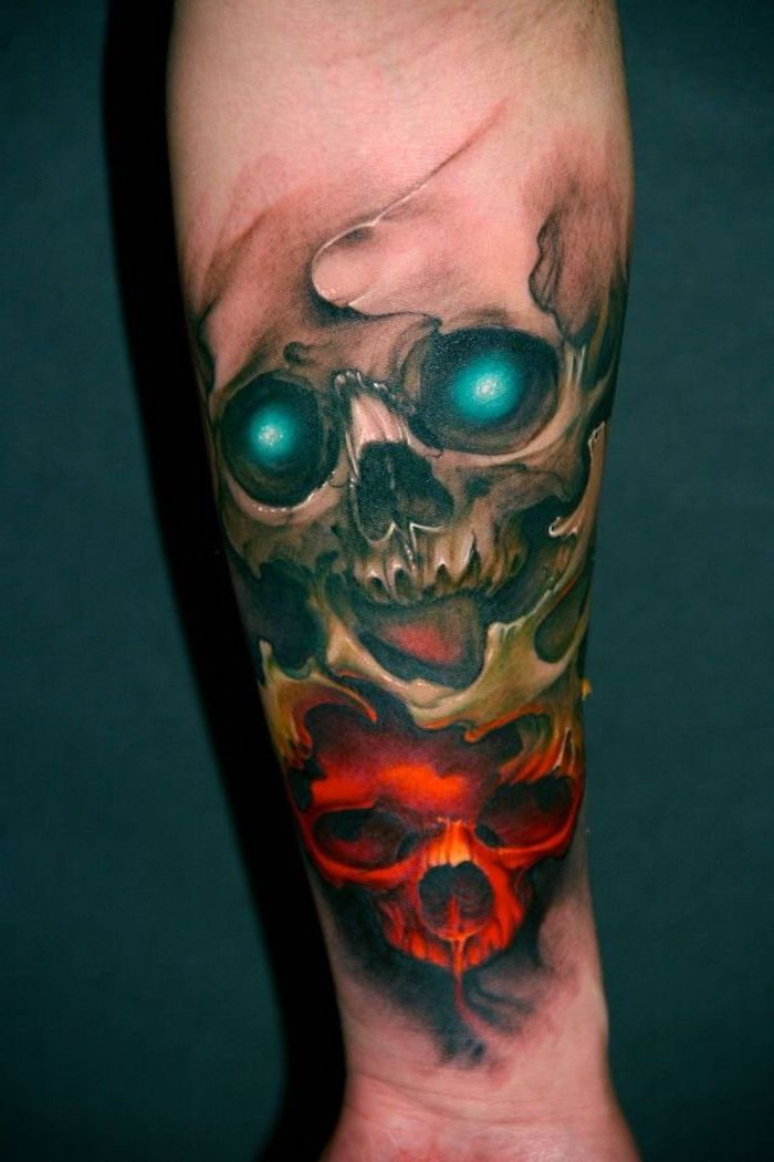 two skulls, colourful forearm tattoo, dark blue background, red and yellow skulls, simple tattoos for men