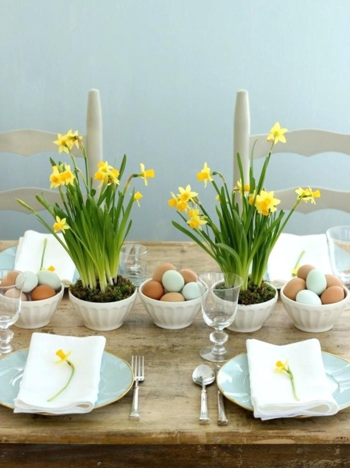 flower bouquets, bowls full of eggs, easter tale centerpieces, blue plates, with white napkins