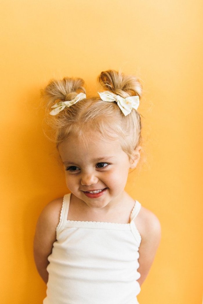 yellow background, kids braided hairstyles with beads, two floral bows, blonde hair in two messy buns