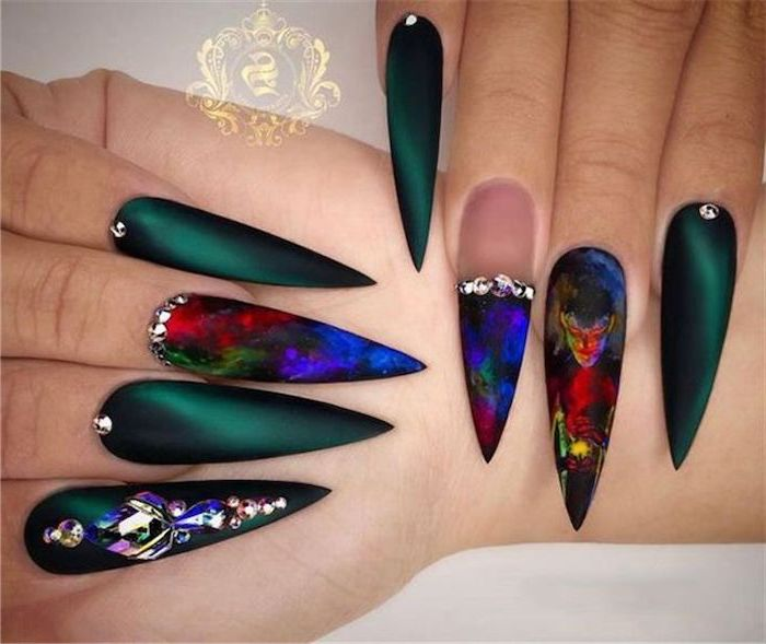 green and black matte nail polish, devil drawings on the nail, manicure ideas, rhinestones on the nails, very long stiletto nails