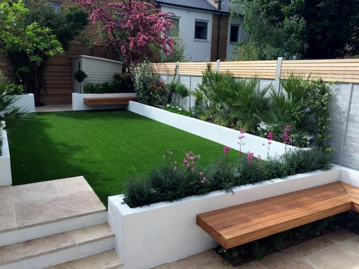 a grass parch, surrounded by planted trees bushes and flowers, small space gardening, wooden bench next to them