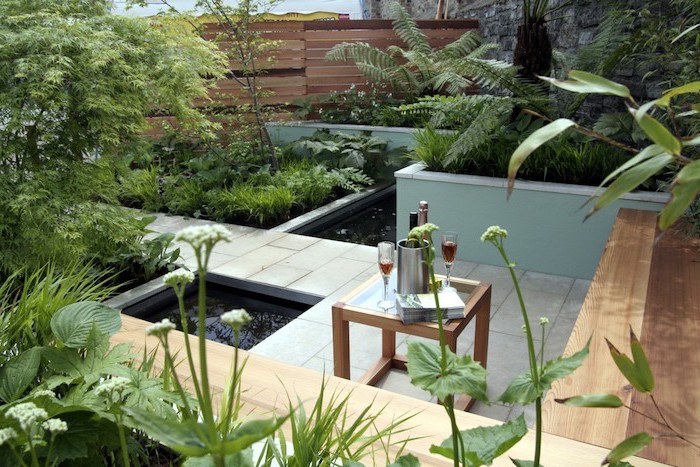 small ponds, cement tiles over it, wooden benches, surrounded by planted bushes and trees, small space gardening