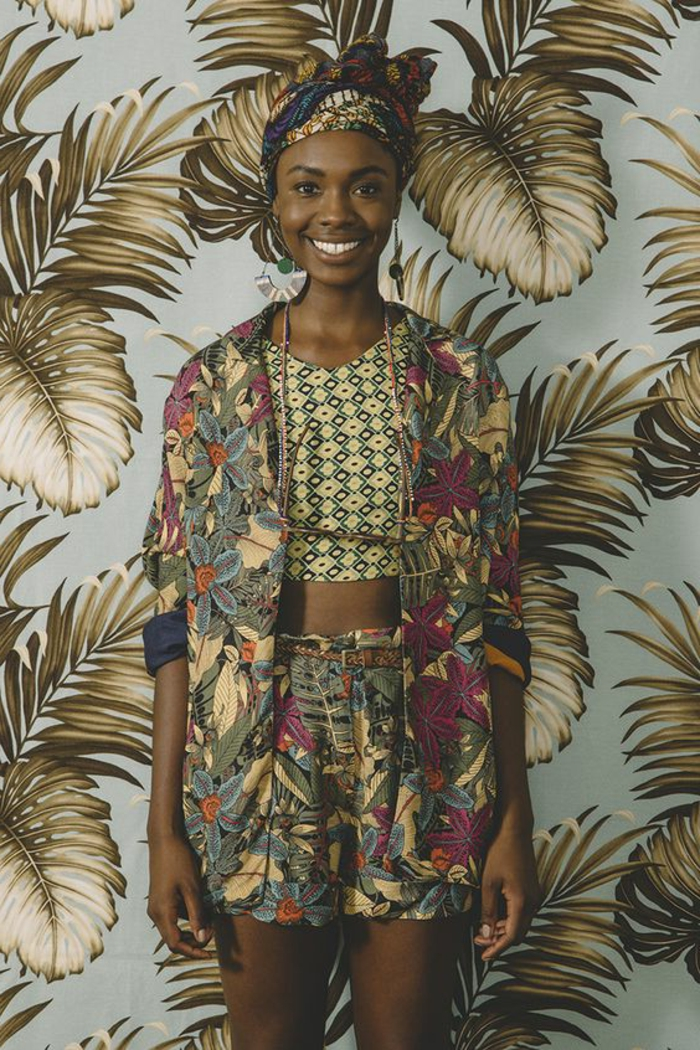 floral wallpaper, woman smiling, wearing a blazer, shorts and crop top, african print dresses, patterned headscarf