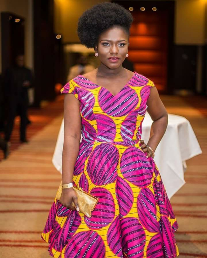 mid length dress, african attire, black hair, in a high updo, golden clutch, table in the background