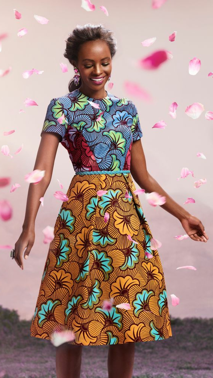 rose petals floating in the air, african print, mid length dress, woman smiling, blue belt