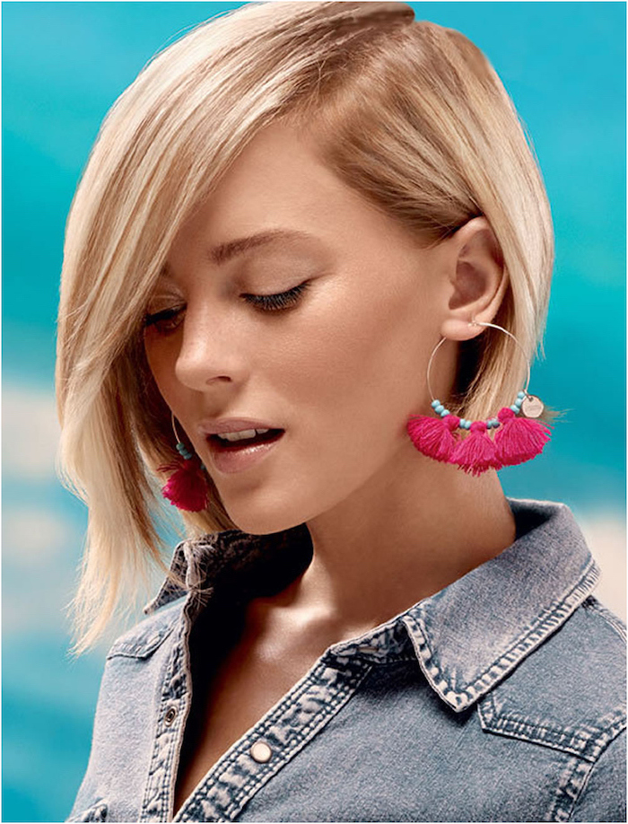 denim shirt, blonde hair, hairstyles for older women, blue background, pink tassel earrings