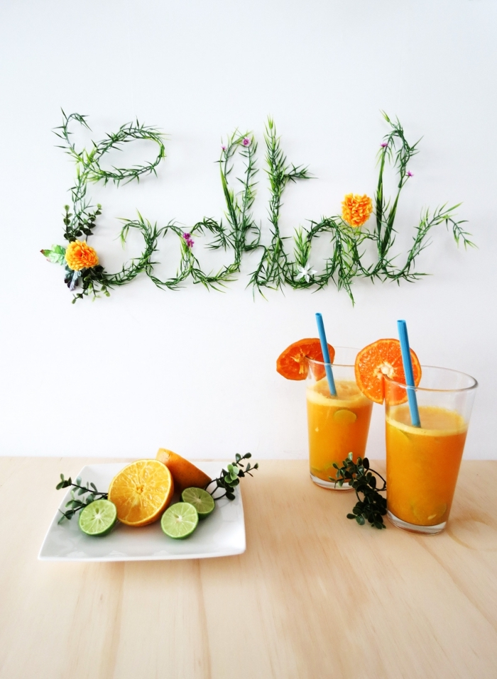cocktail sign, living room wall decor ideas, two glasses, of orange juice, on a wooden table