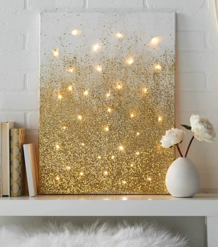 wall art ideas for living room, white canvas, covered in gold glitter, lights behind it, on a white table