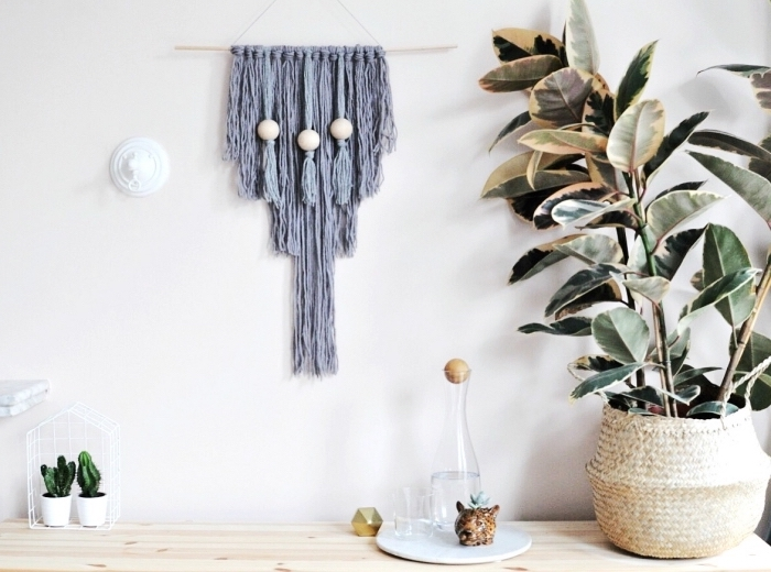 grey macrame wall art, hanging on a white wall, white wall decor, large potted plant on the side, over a wooden table
