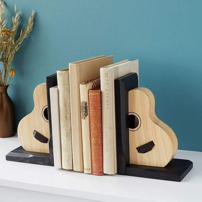 guitar book stoppers, set of books, practical housewarming gifts, blue wall in the background