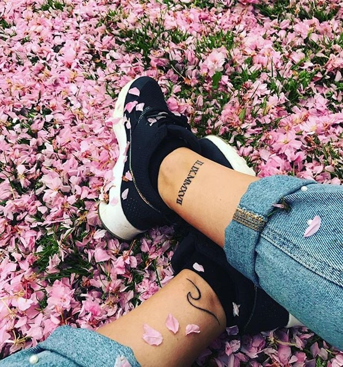 pink flower petals, black sneakers, ankle tattoos, side arm tattoos