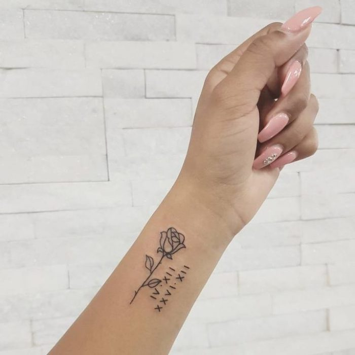long pink nails, rose and numbers, roman numerals translation, wrist tattoo, white tiled wall