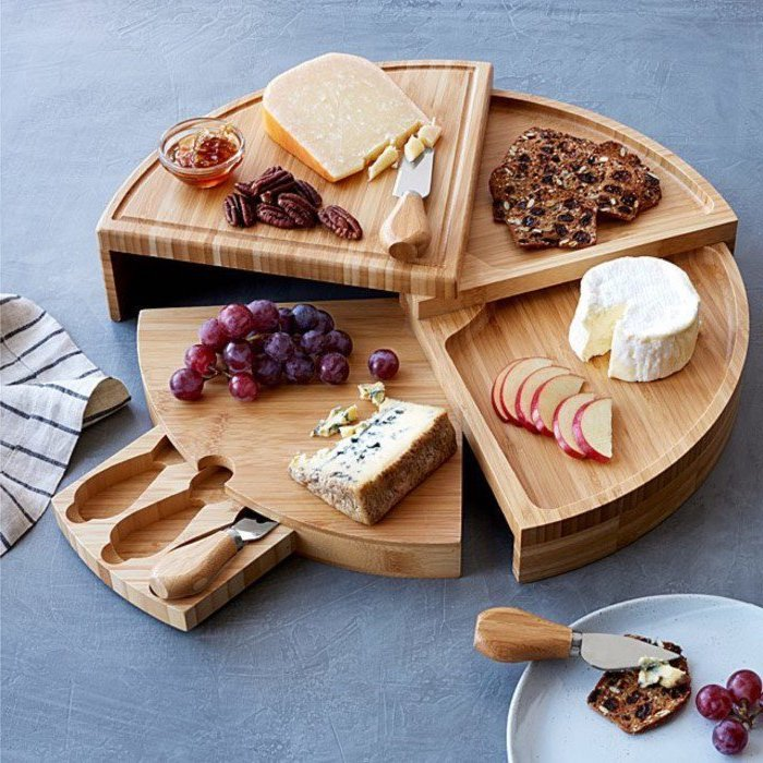 wooden rotating cheese board, what is a good housewarming gift, grapes and cheese, slices of apple, nuts and honey