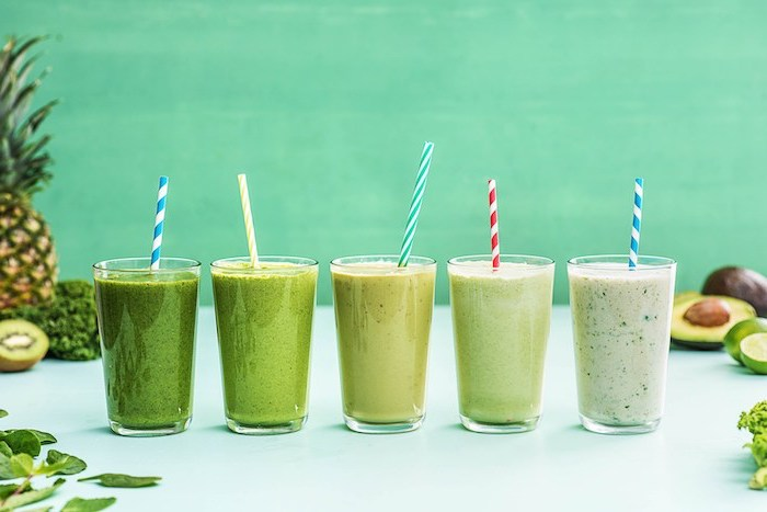 how to make a smoothie, glasses filled with smoothies, in different shades of green, fruits scattered around