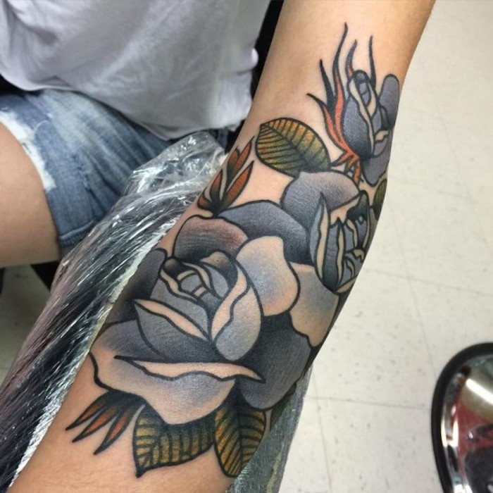 blue roses, arm tattoos for women, grey shirt, short jeans, white tiled floor