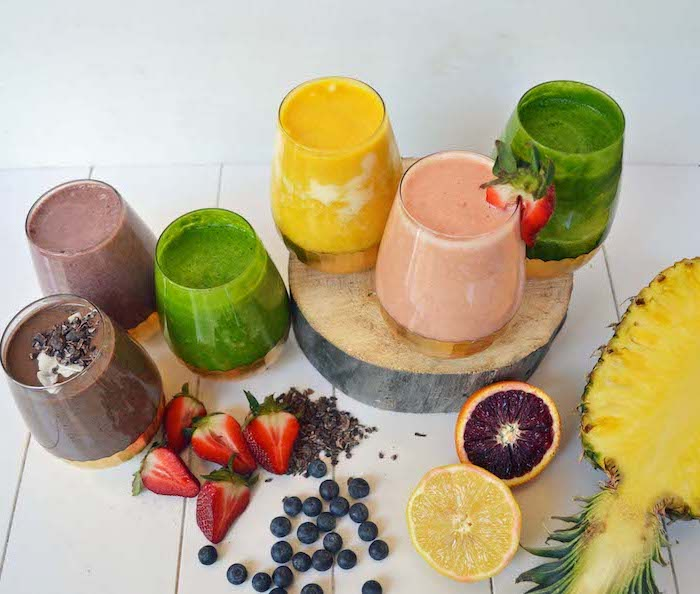smoothies made with different ingredients, how to make a smoothie, sliced fruits, on a wooden table