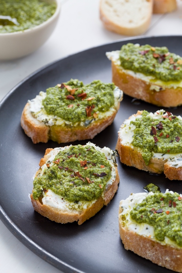 bread slices, with avocado and spinach, on a black plate, dairy free appetizers