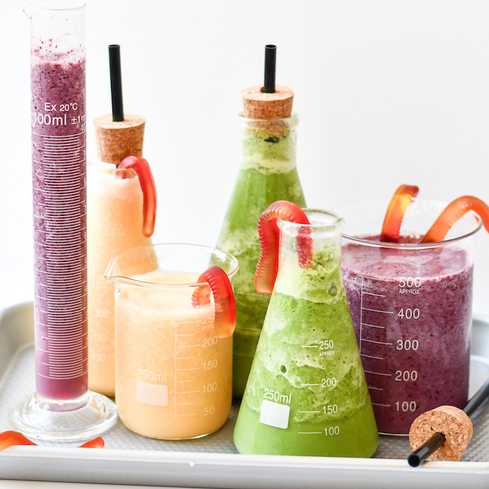 chemistry bottles, filled with smoothies, corks with black straws, smoothie recipes, on white tray