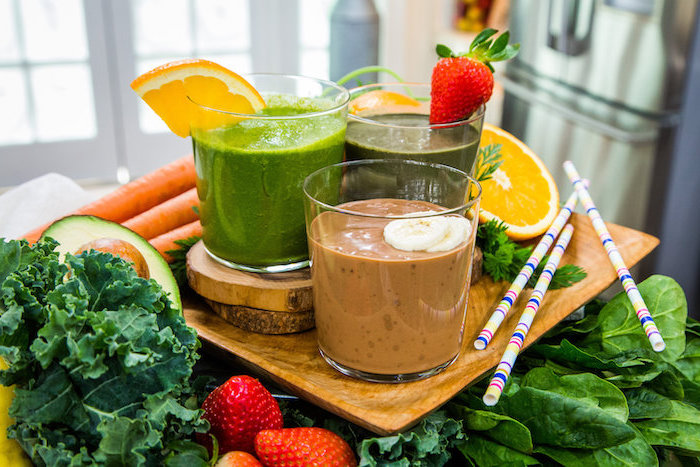 fruits and vegetables around, wooden board, three glasses on top, different ingredients, green smoothie recipe