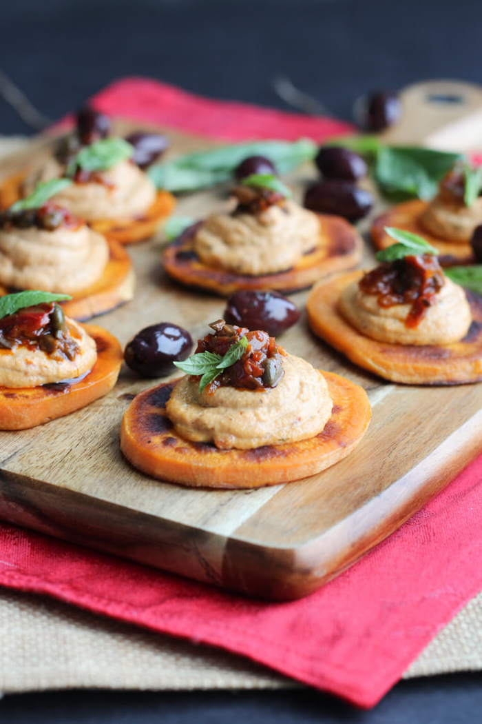 sweet potato slices, hummus and olives on top, veggie appetizers, arranged on a wooden board