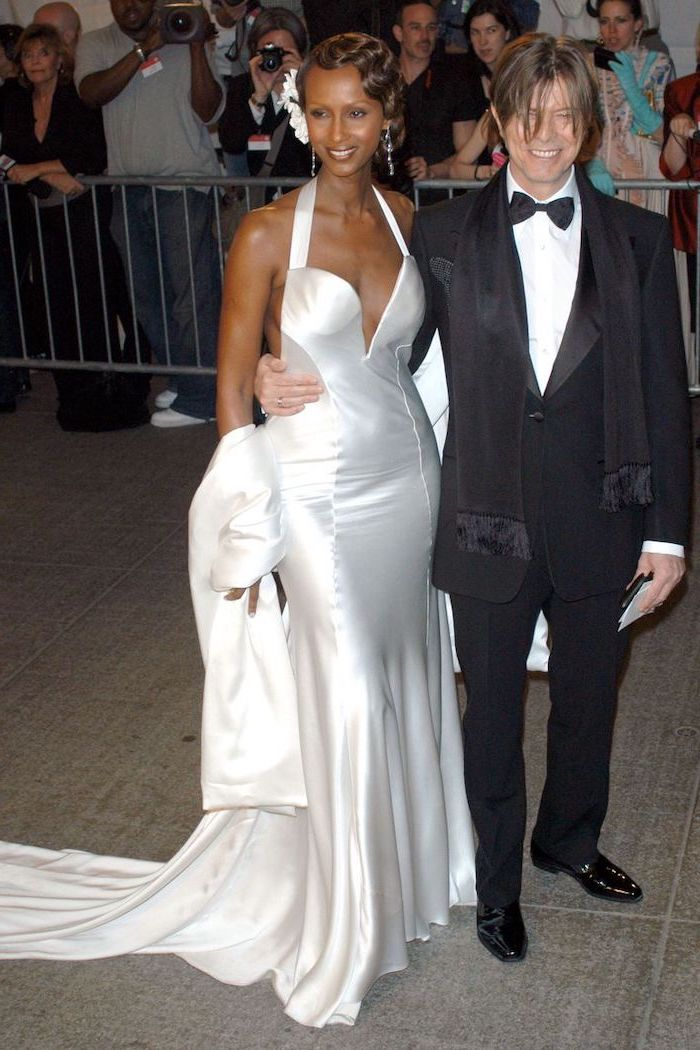 david bowie and iman, met gala best dressed, long white satin dress, retro fashion, brown hair, low updo